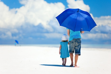 Photo pour Father and daughter at beach with umbrella to hide from sun - image libre de droit