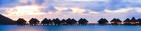 Panorama of over the water bungalows at sunset
