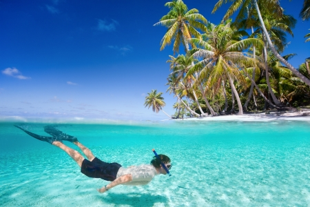 Man swimming in a clear tropical waters in front of exotic island