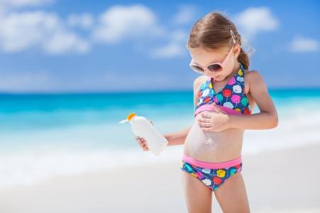 Photo pour Adorable little girl at tropical beach applying sunblock cream - image libre de droit