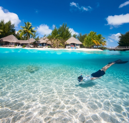 Man swimming in a tropical lagoon in front of exotic island
