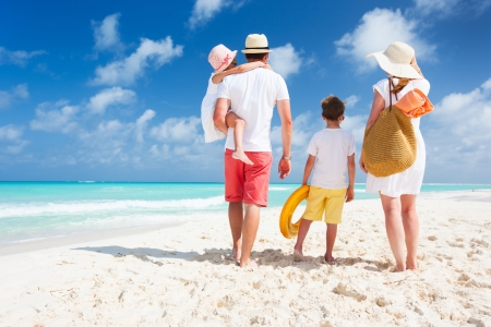 Photo for Back view of a happy family on tropical beach - Royalty Free Image