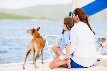 Photo pour Back view of mother, daughter and their pet dog sailing on a luxury yacht or catamaran boat - image libre de droit