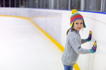 Adorable little girl wearing jeans, warm sweater and colorful hat skating on ice rink