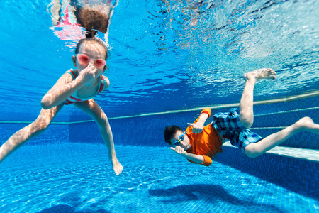 Photo for Kids having fun playing underwater in swimming pool on summer vacation - Royalty Free Image