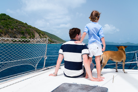 Father, daughter and their pet dog sailing on a luxury yacht or catamaran boat
