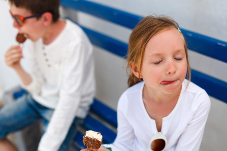 Two adorable kids eating ice cream outdoors on a hot summer day