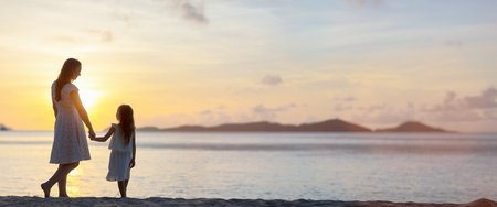Foto de Silhouettes of mother and daughter walking along tropical beach during sunset, panorama with copy space perfect for banners - Imagen libre de derechos