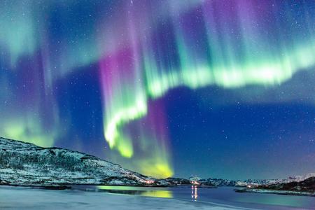 Foto de Incredible Northern lights Aurora Borealis activity above the coast in Norway - Imagen libre de derechos