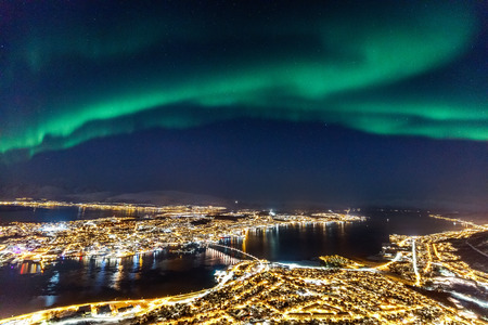 Photo pour Incredible Northern lights Aurora Borealis activity above town of Tromso in Northern Norway - image libre de droit