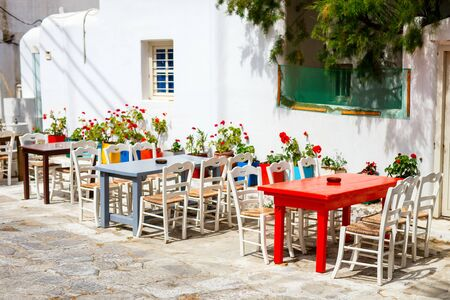 Photo pour Typical greek traditional village on Mykonos Island, Greece, Europe with empty outdoor restaurant tables on street without tourists - image libre de droit