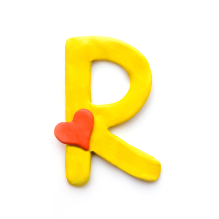 Yellow plasticine letter R English alphabet with red heart meaning love on Valentine's day, isolate on white background