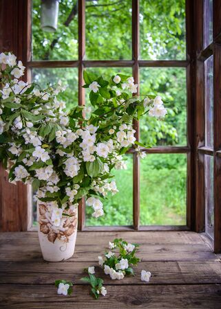 Photo pour A large beautiful bouquet of Jasmine branches in a vase by a wooden window in the countryside - image libre de droit