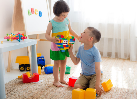 Photo pour A boy and a girl are holding a heart made of plastic blocks. Brother and sister have fun playing together in the room. Preschool children and educational toys - image libre de droit