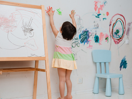 Foto de A little girl, 3 years old, painted an arched look with paint and a brush on the wall of her room. Naughty child, messing around indulge in hooligans. Childhood free space - Imagen libre de derechos