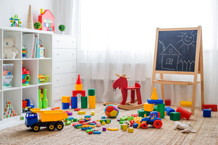 Foto de Children's playroom with plastic colorful educational blocks toys. Games floor for preschoolers kindergarten. interior children's room. Free space. background mock up chalkboard - Imagen libre de derechos