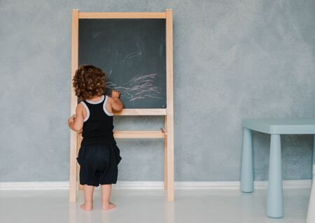 Photo pour small child draws with chalk on a black chalk Board at home in the nursery against a gray wall. Children's educational toys for fine motor skills and thinking. copy space for text. free space - image libre de droit