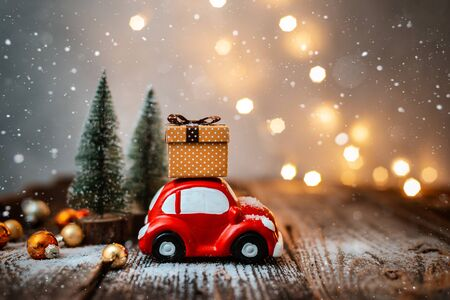 Photo pour New year decoration and background for greetings with free space for text. Toy car carries a gift on the background of Christmas trees and lights bokeh on a wooden. 2020 - image libre de droit