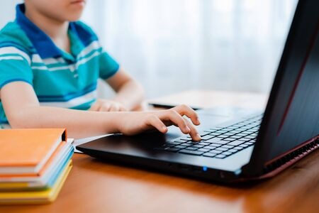 Photo pour Distance learning online education. A schoolboy boy studies at home and does school homework. A home distance learning. - image libre de droit