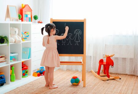 Photo pour A girl stands in the childrens room with a blackboard and draws a family with chalk. concept of family, education, entertainment, games at home, in kindergarten - image libre de droit