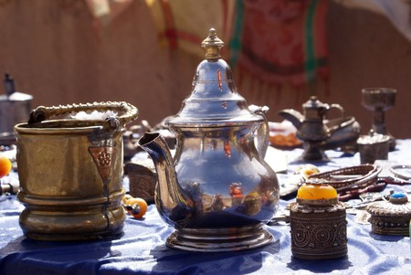 Silver teapot and souvenirs on the table in Morocco