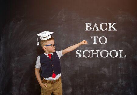 Photo pour Smart kid boy in uniform. Hero child with education cap against blackboard - image libre de droit