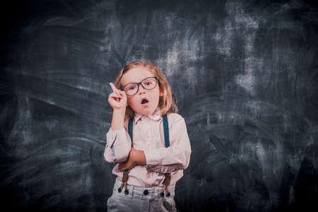 Photo pour Smart little kid ready to go to school. Kid in glasses against blackboard. Back to school - image libre de droit