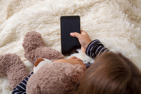 Photo pour Little girl lying on the bed with her favorite teddy bear and playing a smartphone - image libre de droit