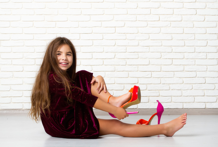 Foto per Little girl sitting on the floor trying on big bright fashionable mother's high-heeled shoes - Immagine Royalty Free