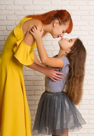 Foto de Little girl gently hugs and stretches to kiss her mom - Imagen libre de derechos