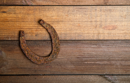 Photo pour a very old and rusty horseshoe symbol of luck on a simple wooden background - image libre de droit