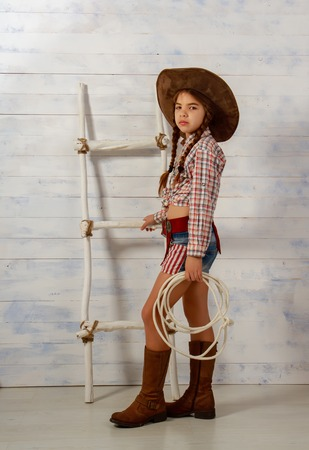 Photo pour Little girl in a wide-brimmed cowboy hat and traditional dress in high boots and with a lasso posing on a light wooden background - image libre de droit