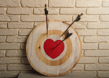 Photo pour Handmade rough wooden target with a center in the form of a red heart and an arrow from a bow that hit the center and two arrows missed. - image libre de droit