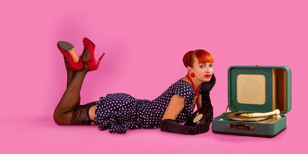 Photo for Pin-up model girl in retro polka-dot dress listens to an old gramophone on a pink background - Royalty Free Image