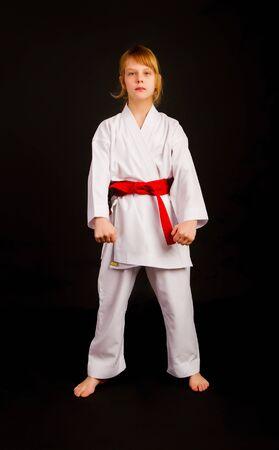 Foto de Little girl in a sports kimono and a red belt performs exercises in kata on a dark background - Imagen libre de derechos