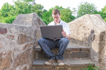 Young man sits on a stair and works on the laptop