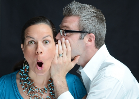 Image of a man telling a secret to a woman