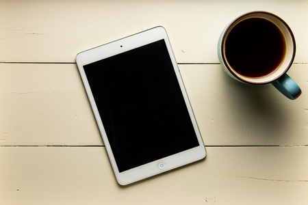 Top view of tablet and coffee on wood