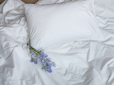 Photo pour Flowers on the messy bed, white bedding items and blue flowers bouqet, creative photo composition with white bed and posy, blue flowers bunch on the beding, romantic bouqet on the bed - image libre de droit