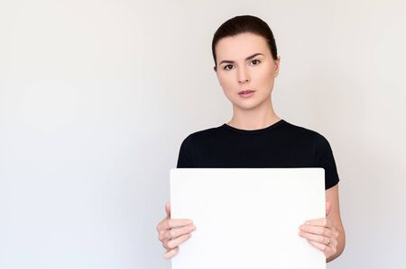 Photo for beautiful woman with dark hair and brown eyes in a black T-shirt on a white background holds a tablet without text. Copy space for text. Portrait medium plan - Royalty Free Image