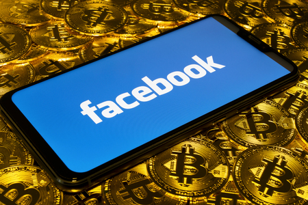 Gold Bitcoin coins pile with the Facebook logo on smartphone screen