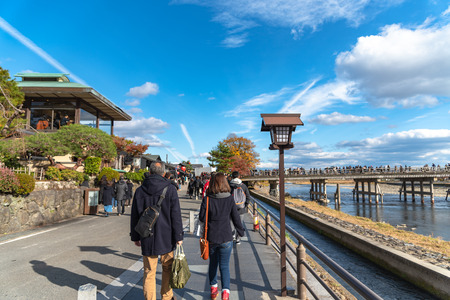 Togetsu-kyo bridge over katsuragawa river with colourful forest mountain background in Arashiyama district. Arashiyama is a nationally designated Historic Site and Place of Scenic Beauty. Kyoto, Japan