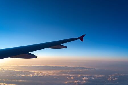 Photo for Up in the air, view of aircraft wing silhouette in dark blue sky horizon and cloud background in sun rise time. from viewed airplane window - Royalty Free Image