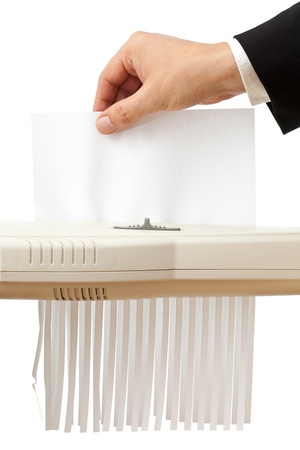 Business man puts single piece of paper in shredder; empty paper with copyspace