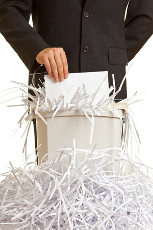 Business man shredding confidential documents at overflowing shredder