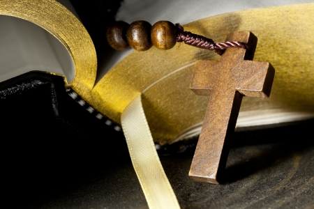 Wooden rosary with cross in front of holy bible