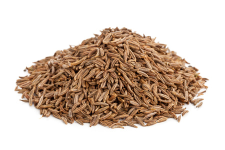 Heap of dried caraway or cumin seeds over white background