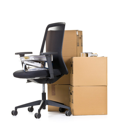 Photo pour Office folder on office chair in front of moving boxes over white background - office moving or relocation concept - image libre de droit