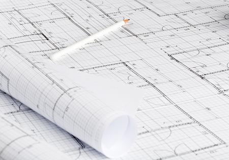 Foto de Rolls of architectural blueprint house building plans on blueprint background on table with pencil - Imagen libre de derechos
