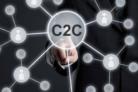 Foto de Executive businessman in suit touching C2C button in network with people icons on virtual touch screen -  consumer to consumer network concept - Imagen libre de derechos